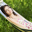 Stock Photo: Young woman in cocktail dress relaxing in a hammock.