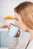 Beautiful caucasian woman is drinking hot drink — Stock Photo