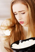 Young depressed woman is eating big bowl of ice creams — Stock Photo