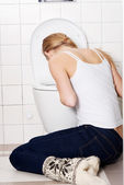 Young caucasian woman is vomiting in the bathroom. — Stock Photo