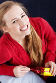 Beautiful caucasian woman in red sweater is unwrappind small present — Stock Photo