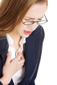 Beautiful business woman touching her chest, feeling unwell. — Stock Photo