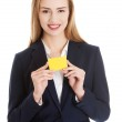 Beautiful caucasian business woman holding yellow empty personal card — Stock Photo #39580071