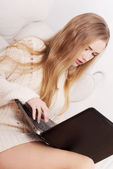 Beautiful caucasian woman in bright sweater is writing on laptop — Stock Photo