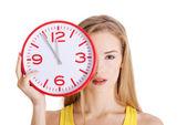Beautiful caucasian casual woman holding red clock. — ストック写真