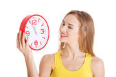 Beautiful caucasian casual woman holding red clock. — Stock Photo