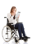 Beautiful casual woman sitting on w wheelchair with tablet. — Stock Photo