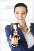 Young business woman with hourglass — Stock Photo