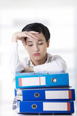 Sad woman with ringbinders sitting at the desk. — Stock Photo