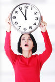 Shocked woman holding office clock — Stock fotografie