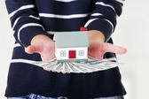 Woman holding US dollars bills and house — Stock Photo