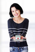 Woman holding US dollars bills and house model — Stock Photo