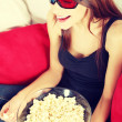 Beautiful young woman watching TV in 3d glasses — Stock Photo
