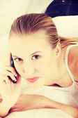 Pretty woman with mobile phone lying on bed — Stock Photo