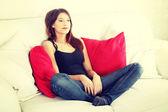 Young sad woman sitting on sofa — Stock Photo
