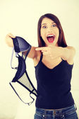 Angry woman with bra in hand. — Stock Photo
