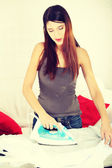 Happy young woman ironing — Stock Photo
