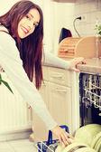 Jovem mulher na cozinha fazendo trabalhos domésticos. — Fotografia Stock