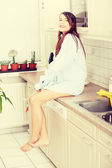 Young happy beautiful woman sitting on kitchen counter — Stock Photo