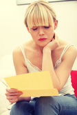 Worried woman's reading letter — Stock Photo