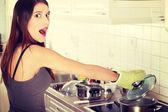 Ung kvinna koka något i potten — Stockfoto