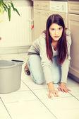 Ung kvinna rengöring flor — Stockfoto