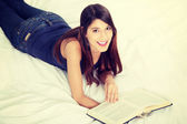 Woman reading a book on the bed — Stock Photo