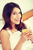 Woman in bed drinking orange juice — Stock Photo