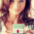 Young woman holding euros bills and house model — Stock Photo