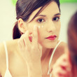 Beautiful woman applying cream on face — Stock Photo