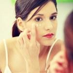 Beautiful woman applying cream on face — Stock Photo