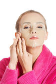 Woman in pink bathrobe with collagen mask. — Stock Photo