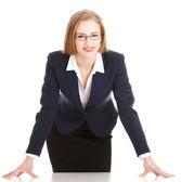 Young attractive business woman bending over table. — Stock Photo