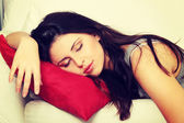 Beautiful woman is sleeping on red pillow. — Stock Photo