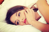 Young sad girl lying in bed. — Stock Photo