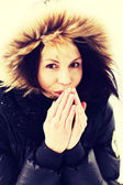 Woman trying to warm her hands with a breath — Stockfoto