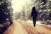 Woman is walking through forest in wintertime — Stock Photo