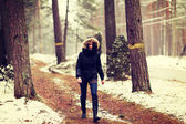Woman is walking through forest in wintertime. — Stock Photo