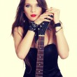 Attractive girl sitting with electric guitar. — Stock Photo