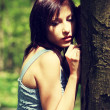 Young woman standing next to tree — Stock Photo #40201011