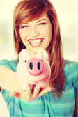Teen woman showing her pink piggy bank — Stock Photo