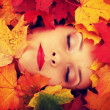 Woman face in autumn leafs — Stock Photo