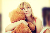 Kid embraces teddy bear — Stock Photo
