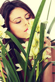 Beautiful young woman smelling orchid flower — Stock Photo