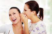 Två unga flickvänner talar rummors — Stockfoto