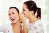 Two young girlfriends talking rummors — Stock Photo