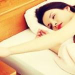 Woman turning off an alarm clock — Stock Photo