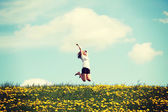 Woman jumping on blossom meadow. — Stock Photo