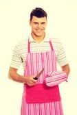 Man wearing a pink kitchen apron. — Stock Photo