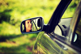 Woman driving the car which is visible in mirror. — Photo